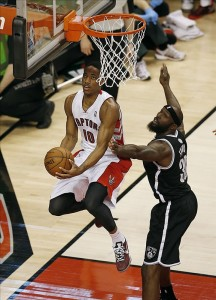 Demar Derozan of Raptors goes up and under Reggie Evans