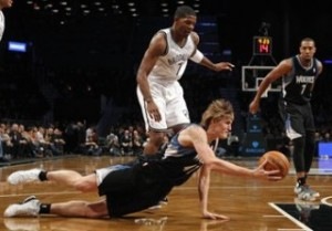 Minnesota Timberwolves forward Kirilenko looks to pass the ball as he falls to the fall in front of teammate Williams and Brooklyn Nets guard Johnson in the first quarter of their NBA basketball game in New York