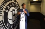 Bojan Bogdanovic posing in front of Nets logo with uniform during his presser